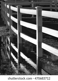 A reflection of a white fence in a pool of water after a storm  in black and white