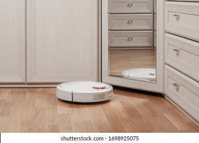 reflection of white robot vacuum cleaner running before mirror in bedroom. modern smart appliance for cleaning house.