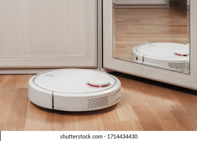 reflection of white robotic vacuum cleaners. modern smart appliance for cleaning house.