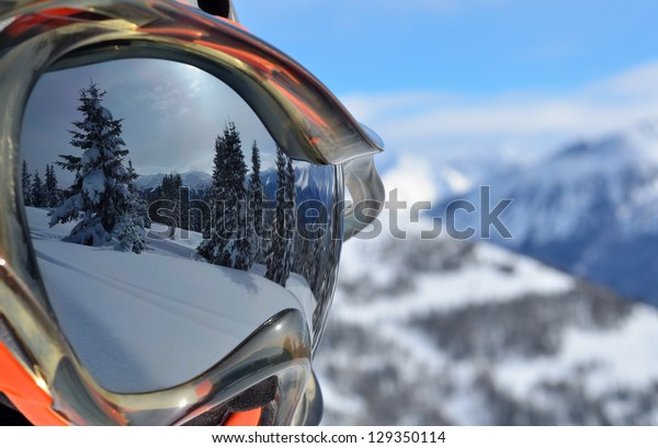 Reflection of the winter mountain landscape in a ski mask. Shallow depth of field.