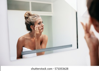 Reflection of a woman in bathroom mirror applying cosmetic cream on her face. Female putting on moisturizer on her face skin.