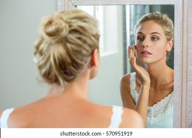 Reflection of woman checking her skin in bathroom mirror
