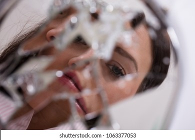 Reflection Of A Woman's Face In Broken Mirror