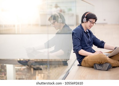 Reflection of young Asian business man enjoy listening to music by headphones while using laptop computer in co working space. freelance or digital nomad lifestyle in urban workspace concepts