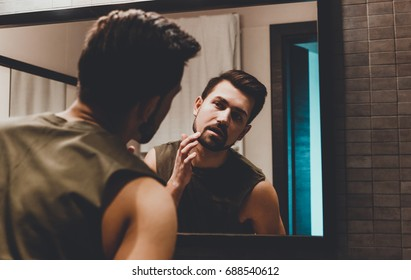Reflection of young man in bathroom mirror looking on his face