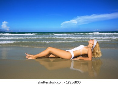 Reflection of Young woman on the tropical beach.
