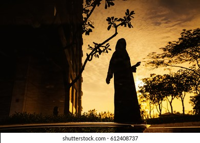 reflection of a young woman wearing a hijab  standing near a water body at dusk