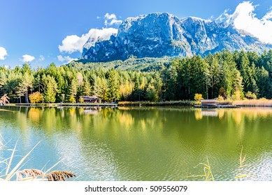 reflections of autumn trees on the lake plateau of sciliar in the Tyrolean Dolomites in Trentino Alto dige Italy