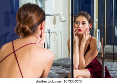Reflections of beautiful young woman in red dress with naked back, sitting on bed in front of the mirror, beauty fashion concept