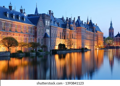 Reflections of the Binnenhof (13 century gothic castle) on the Hofvijver lake at dusk during the blue hour, with the clock tower of Grote of Sint Jacobskerk on the right, The Hague, Netherlands