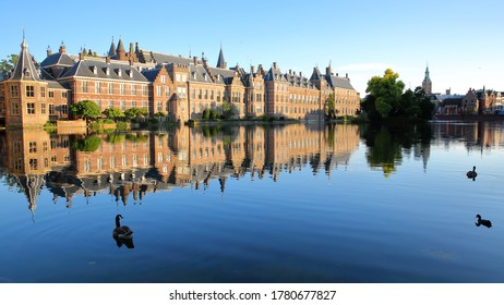 Reflections of the Binnenhof (13 century gothic castle) on the Hofvijver lake, with the clock tower of Grote of Sint Jacobskerk on the right, The Hague, Netherlands