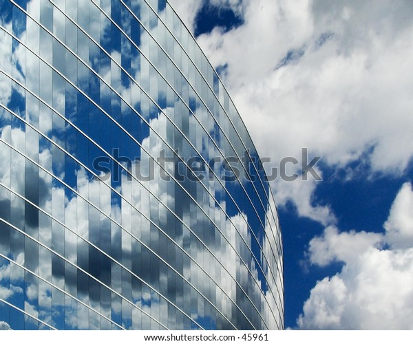 Reflections of clouds in glass building.