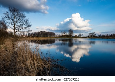 reflections of country farm house and clouds in the lake water