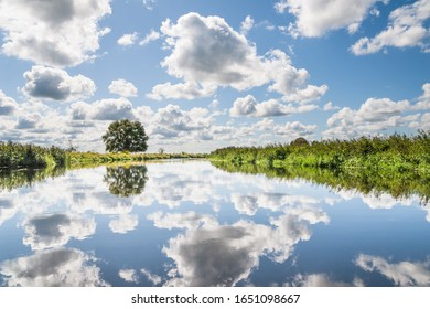 Reflections of cumulus clouds in water of Biebrza river in sunny summer day, Podlasie, Poland