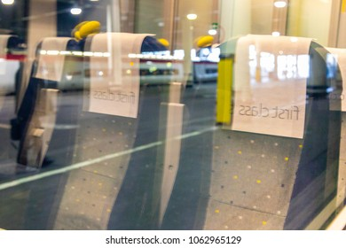 Reflections of empty first class train seats at London Euston railway station.  Blurred train and commuter. West Midlands Trains. London, UK - 3rd April 2018.