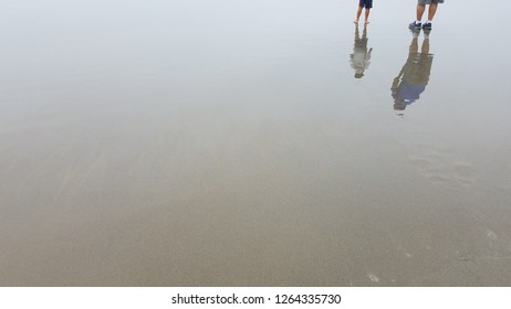 reflections of father and son walking on wet sand on beach with water