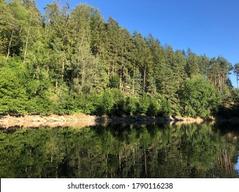 Reflections of a forest in a lake on a beautiful summer day with clear blue sky in the background