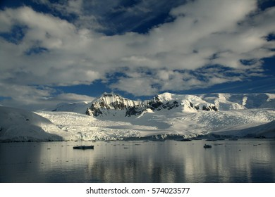 Reflections of glacial icefalls and mountains, with cloudy blue sky  		Lemaire Channel,	Antarctica