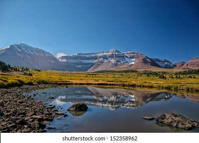 Reflections in a high mountain pond of  Kings Peak highest mountain  in Utah in late autumn/ Pond in Henry Fork Basin