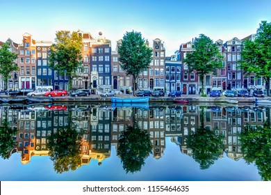Reflections of iconic buildings along an Amsterdam canal