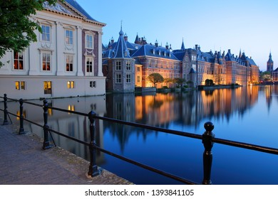 Reflections of the Mauritshuis and the Binnenhof (13 century gothic castle) on the Hofvijver lake at dusk during the blue hour, with the clock tower of Grote of Sint Jacobskerk on the right, The Hague
