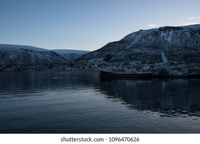 Reflections of the mountains in the ice cold water of a fjord around Tromso, Norway