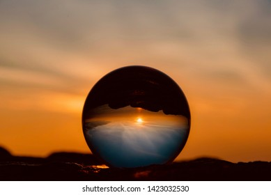 reflections on the glass sphere with warm colors of dawn over the San Francisco Bay in California United States