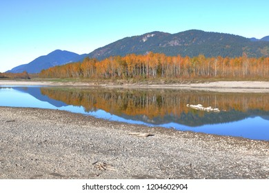 Reflections on a shallow river during a bright, autumn day expose sandbars and the riverbank after a dry summer in the Canadian wilderness.