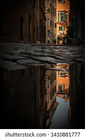 REFLECTIONS IN A PUDDLE AT A STREET IN ROME, ITALY AUGUST 15 2016 . TOURIST COUPLE WALKING AWAY