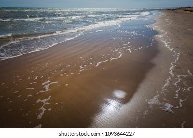 Reflections the shoreline sea water of a sandy beach, Bibione, Veneto, Italy