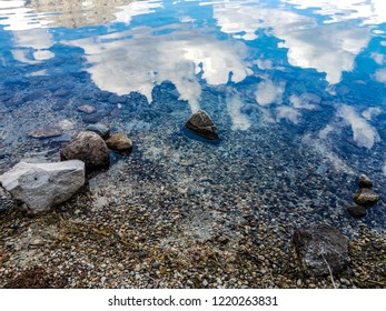 The reflections of the sky and clouds are shown in this image, taken by the rocky shoreline of Leigh Lake in the Grand Teton National Park in Wyoming.