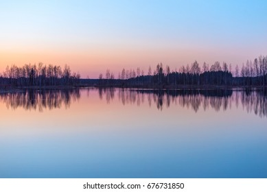 Reflections of tree silhouettes on a lake