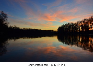 Reflections of tree in the water at sunset - Shutterstock ID 1049474144