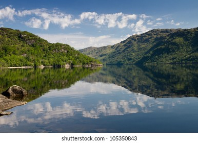 Reflections of trees and clouds on Loch Lomond, Scotland, United Kingdom
