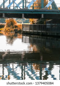 Reflections in water of the River Cam under the railway bridge with walkway.
