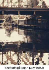 Reflections in water of the River Cam under the railway bridge with walkway. Sepia tone.