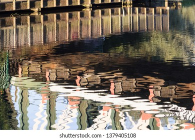 Reflections in water of the River Cam under the railway bridge with walkway. Horizontal abstract crop.