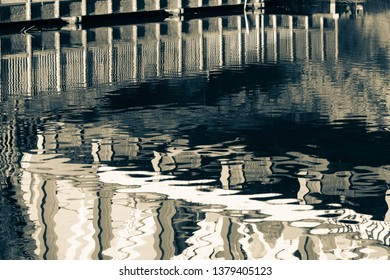Reflections in water of the River Cam under the railway bridge with walkway. Horizontal crop for abstract design.