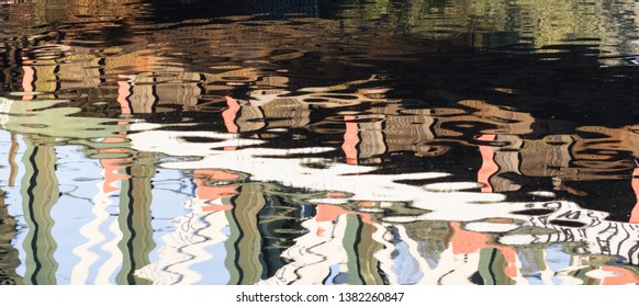Reflections in water of the River Cam under the railway bridge with walkway. Long horizontal crop for abstract design.