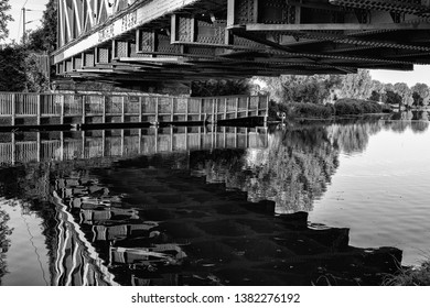 Reflections in water of the River Cam under the railway bridge in East Chesterton, Cambridge. With wooden walkway into countryside beyond. Black and White photo.