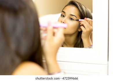 Reflective mixed race young woman with brush eye liner on with looking in the mirror