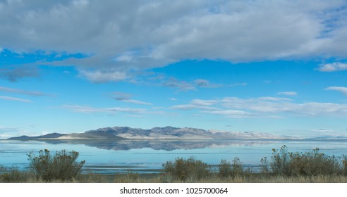 Reflective mountain gleaming off of Salt Lake in Utah during winter.  Beautiful blue skies with puffy clouds