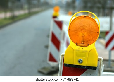 Reflective roadblock or construction site lock with signal lamp on a road. Red and white street barricade.
