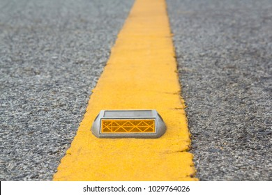 reflector on yellow line on road, trafic equipment background