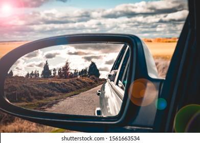 Reflejo en el espejo retrovisor del automóvil, selfie, retrato, autorretrato, mano, brazo. Paz, calma, tranquilidad, puesta de sol. paseo en coche
