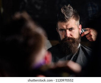 Reflexion of barbers hand with hair clipper trimming nape of client. Hipster bearded client getting hairstyle in front of mirror. Barber with hair clipper trimming nape, defocused. Barbershop concept.