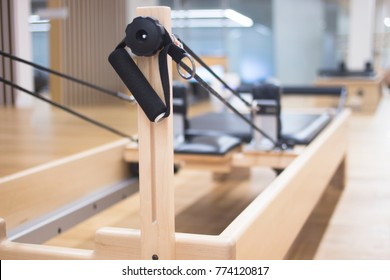 Reformer pilates studio machine for fitness workouts in gym.