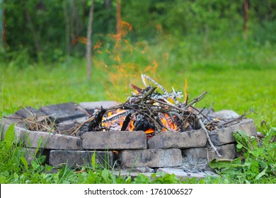Refractory brick fireplace in focus and blurry bonfire in the background