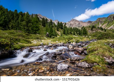 Refreshed small brook river stream flowing over gravel bed with stunning mountain scenery in background. Concept: Refreshing, pure, water quality, holiday