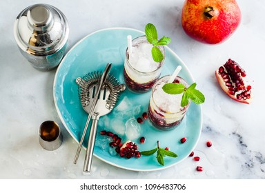 refreshing alcoholic drink with lemon and pomegranate seeds on a white stone table and gray background with mint and bar accessories
